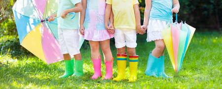 Enfants dans des bottes de pluie. Groupe d'enfants de la maternelle dans des bottes en caoutchouc colorées et des vestes d'automne. Chaussures pour chutes de pluie. Usure des pieds pour enfant et bébé. Tout-petit dans les poissons. Gumboots arc-en-ciel. Mode enfantine Banque d'images - 87015337