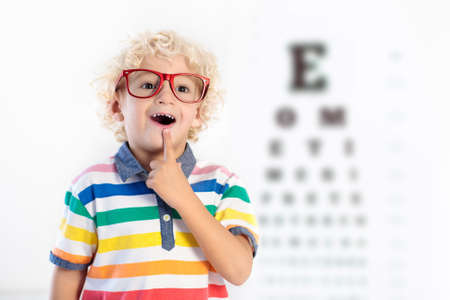 Child at eye sight test. Little kid selecting glasses at optician store. Eyesight measurement for school kids. Eye wear for children. Doctor performing eye check. Boy with spectacles at letter chart. Stock Photo