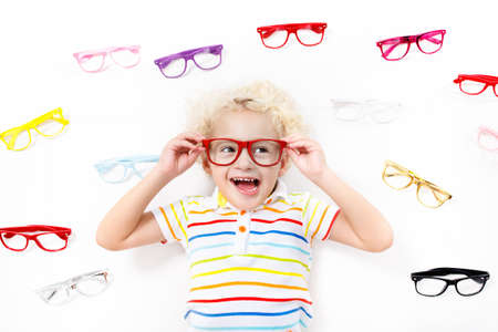 Child at eye sight test. Little kid selecting glasses at optician store. Eyesight measurement for school kids. Eye wear for children. Doctor performing eye check. Baby with spectacles top view.