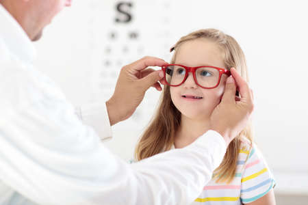 Kind bei Augensichtprüfung. Kleinkind, das Gläser am Optikerspeicher vorwählt. Augenmaß für Schulkinder. Augenschutz für Kinder. Doktor, der Augenprüfung durchführt. Mädchen mit Schauspielen am Briefdiagramm.