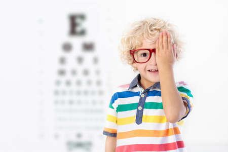 Niño a prueba de vista. Niño seleccionando gafas en la tienda de óptica. Medición de la vista para escolares. Gafas para niños. Doctor realizando control ocular. Niño con gafas en carta carta. Foto de archivo