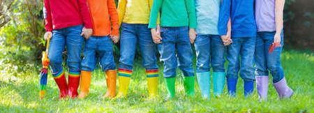 Niños en botas de lluvia. Grupo de niños del jardín de la infancia en cargadores de goma coloridos y chaquetas del otoño. Calzado para lluvia. Desgaste del pie para el niño y el bebé. Niño en wellies. Arco iris gumboots. Moda para niños