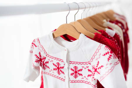 Clothes rack with red Christmas knit wear. Wardrobe with knitted winter jumper and dress. Xmas clothing collection. Christmas gifts shopping. Winter sale for children wear. Kids clothing shop. Zdjęcie Seryjne - 87073496