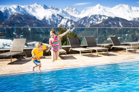Little kids play in outdoor swimming pool of luxury alpine resort in Alps mountains, Austria. Winter and snow vacation with children. Hot tub outdoors with mountain view. Boy and girl play and swim.