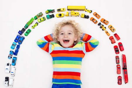 clutter: Funny curly toddler boy playing with his model car collection on the floor. Transportation and rescue toys for children. Rainbow toy mess in kids room. View from above. Many cars for little boys.