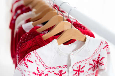 Clothes rack with red Christmas knit wear. Wardrobe with knitted winter jumper and dress. Xmas clothing collection. Christmas gifts shopping. Winter sale for children wear. Kids clothing shop. Banco de Imagens