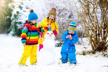 Les enfants construisent un bonhomme de neige. Enfants construisant l'homme de neige jouant à l'extérieur le jour d'hiver ensoleillé neigeux. Plaisir en famille en plein air pendant les vacances de Noël. Garçon et fille jouent des boules de neige. Vêtements d'hiver pour bébé et enfant en bas âge.