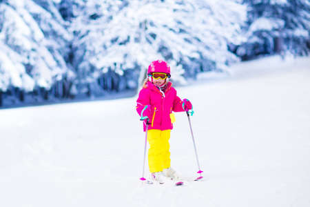 skiers: Family ski vacation. Group of skiers in Swiss Alps mountains. Mother and child skiing in winter. Parents teach kids alpine downhill skiing. Ski gear and wear, safe helmets. Stock Photo