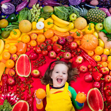 cucumbers: Little girl with variety of fruit and vegetable. Colorful rainbow of raw fresh fruits and vegetables. Child eating healthy snack. Vegetarian nutrition for kids. Vitamins for children. View from above.