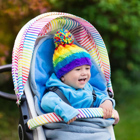 Baby in stroller on a walk in autumn park. Adorable little boy with knitted hat and jacket sitting in colorful pushchair under warm blanket. Fall outdoor fun for kids. Child in buggy on winter stroll. Stock Photo
