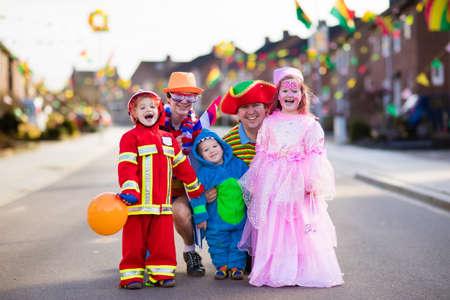 Les enfants et les parents sur le truc ou le régal de Halloween. Famille en costumes d'Halloween avec des sacs à doigts marchant dans un tour ou un traitement de rue décoré. Bébé et enfant d'âge préscolaire célèbrent le carnaval. Costume d'enfant. Banque d'images - 87335542