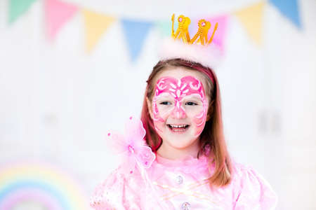kids birthday party: Face painting for little girl. Princess and fairy theme birthday party with face paint artist and costume for preschool child. Kids celebrating Halloween or carnival with pink dress and crown. Stock Photo