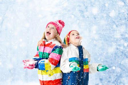 Bambini che giocano in neve. I bambini giocano all'aperto durante la giornata invernale innevata. Ragazzo e ragazza che cattura i fiocchi di neve in nevicata tempesta. Fratello e sorella gettando palline da neve. Attività di vacanza di famiglia a Natale. Archivio Fotografico - 87335544