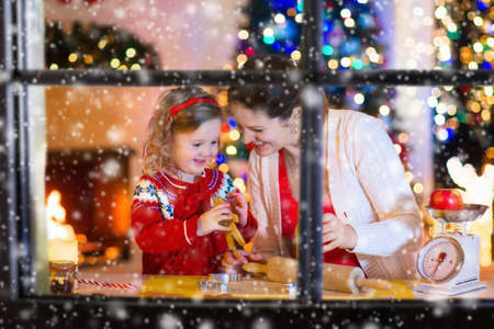 candle: Mother and little girl baking Christmas pastry. Children bake gingerbread. Toddler child preparing cookie for family dinner on Xmas eve. Decorated kitchen or dining room with fireplace, tree, candles. Stock Photo
