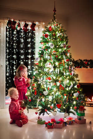 Children at Christmas tree and fireplace on Xmas eve. Family with kids celebrating Christmas at home. Boy and girl in matching sweater decorating xmas tree and opening presents. Holiday gifts for kid.