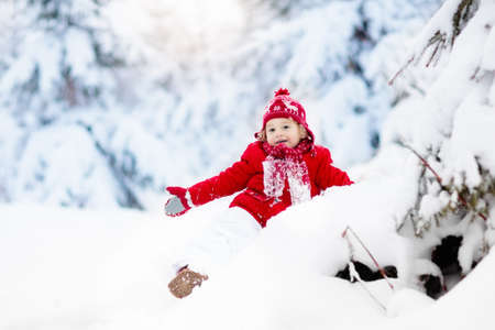 Child playing with snow in winter. Little boy in colorful jacket and knitted hat catching snowflakes in winter park on Christmas. Kids play and jump in snowy forest. Toddler jumping in snowdrift. Stock Photo
