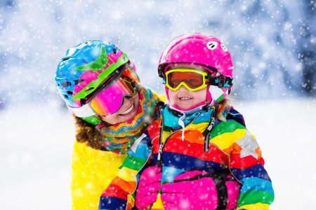 Family ski vacation. Group of skiers in Swiss Alps mountains. Mother and child skiing in winter. Parents teach kids alpine downhill skiing. Ski gear and wear, safe helmets. Archivio Fotografico