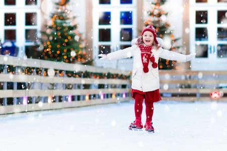 Patin à glace pour enfants dans la patinoire de Winter Park. Enfants patin à glace sur la foire de Noël. Petite fille avec des patins sur une froide journée enneigée. Plaisir de neige en plein air pour enfant. Sports d'hiver. Activité de vacances de Noël avec enfant.