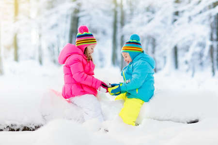 Kids playing in snow. Children play outdoors on snowy winter day. Boy and girl catching snowflakes in snowfall storm. Brother and sister throwing snow balls. Family Christmas vacation activity. Stock Photo