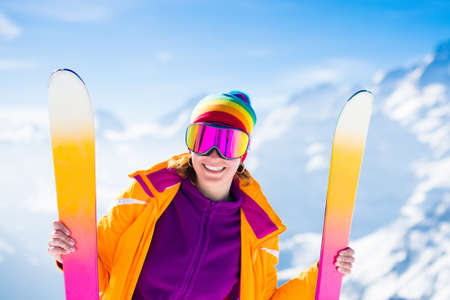 Young active woman skiing in mountains. Female skier kid with safety helmet, goggles and poles enjoying sunny winter day in Swiss Alps. Ski race for adults. Winter and snow sport in alpine resort. Standard-Bild