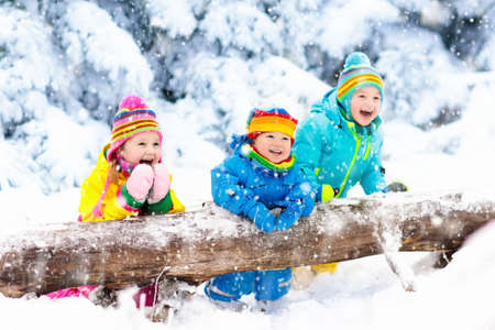 Kinder spielen im Schnee. Kinder spielen draußen am Tag des verschneiten Winters. Anziehende Schneeflocken des Jungen und des Mädchens im Schneefalle stürmen. Bruder und Schwester, die Schneebälle werfen. Familienweihnachtsferienaktivität. Standard-Bild