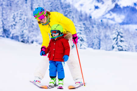 Family ski vacation. Group of skiers in Swiss Alps mountains. Mother and child skiing in winter. Parents teach kids alpine downhill skiing. Ski gear and wear, safe helmets. Standard-Bild