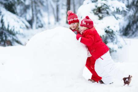 palle di neve: I bambini costruiscono pupazzo di neve. Bambini che costruiscono neve che gioca all'aperto all'aperto sulla giornata di sole invernale nevoso. Divertimento di famiglia all'aperto durante la vacanza di Natale. Ragazzo e ragazza giocare palla di neve. Abbigliamento invernale per bambino e bambino. Archivio Fotografico