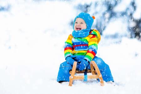 Weinig jongen die van een arrit geniet. Kindersleeën. Peuterjong geitje die een slee berijden. Kinderen spelen buiten in de sneeuw. Kinderen slee in de bergen van de Alpen in de winter. Outdoor plezier voor familie Kerstvakantie.