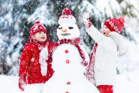 Dzieci budują snowman. Dzieci budynku człowiek śniegu grając na zewnątrz w słoneczny dzień zimowy śnieg. Odkryta rodzina zabawy na wakacje Bożego Narodzenia. Chłopiec i dziewczynka grać kule śniegu. Zimowe ubrania dla niemowląt i małych dzieci.