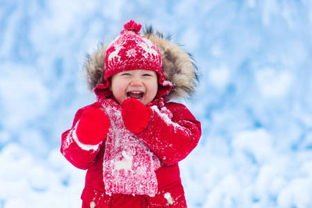 Baby playing with snow in winter. Little toddler boy in red jacket and Xmas reindeer knitted hat catching snowflakes in winter park on Christmas. Kids play in snowy forest. Children catch snow flakes Reklamní fotografie - 87954471