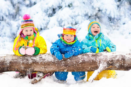 Kids playing in snow. Children play outdoors on snowy winter day. Boy and girl catching snowflakes in snowfall storm. Brother and sister throwing snow balls. Family Christmas vacation activity. Banco de Imagens