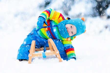 そりに乗るを楽しんでいる小さな男の子。そりの子。幼児の子供がそりに乗って。雪の中で子供を促します。子供たちは冬のアルプス山脈のそり。