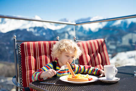 Tired sleepy child in outdoor restaurant in the mountains. Family having apres ski lunch in alpine resort. Kids eat after skiing. Winter snow fun for child. Food and drink after sport. Mountain view. Stock Photo