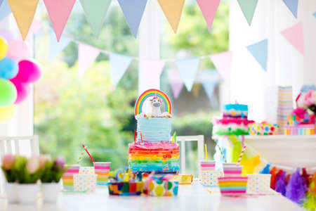 Kids birthday party decoration and cake. Decorated table for child birthday celebration. Rainbow unicorn cake for little girl. Room with festive balloons, colorful banners in baby pastel color.