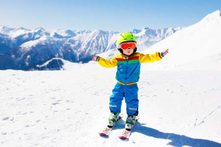 Child skiing in the mountains. Kid in ski school. Winter sport for kids. Family Christmas vacation in the Alps. Children learn downhill skiing. Alpine ski lesson for boy or girl. Outdoor snow fun. Stock Photo