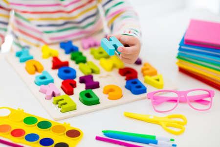 Dziecko odrabiania lekcji do szkoły przy białym biurku. Drewniane puzzle edukacyjne ABC dla dzieci. Szczęśliwy powrót do szkoły. Dziecko uczące się liter alfabetu. Mała dziewczynka z przyborami szkolnymi i książkami.