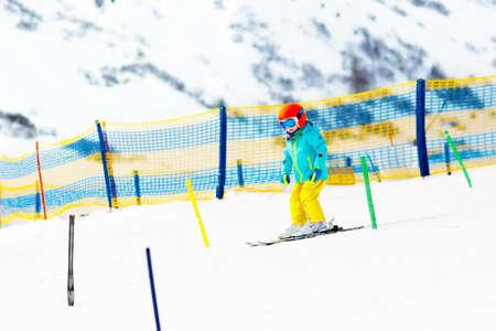 어린이 산속에 스키입니다. 스키 학교에서 키드. 아이들을위한 겨울 스포츠. 알프스에서 가족 크리스마스 휴가입니다. 아이들은 내리막 길을 배우게됩 스톡 콘텐츠