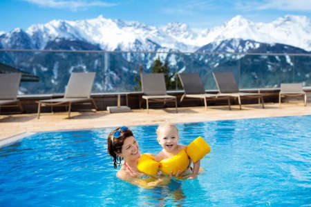 Mother and baby play in outdoor swimming pool of luxury spa alpine resort in Alps mountains, Austria