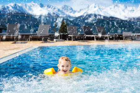 Little child playing in outdoor swimming pool of luxury alpine resort in the Alps mountains, Austria