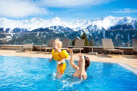 母親と赤ちゃんはオーストリア、アルプスの山に高級スパ アルペン リゾートの屋外プールで遊ぶ