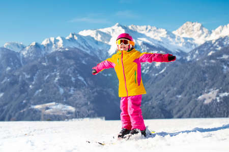 Child skiing in the mountains. Kid in ski school. Winter sport for kids. Family Christmas vacation in the Alps. Children learn downhill skiing. Alpine ski lesson for little girl. Outdoor snow fun.