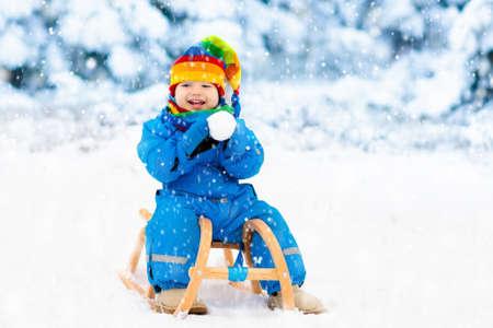 Weinig jongen die van een arrit geniet. Kindersleeën. Peuterjong geitje die een slee berijden. Kinderen spelen buiten in de sneeuw. Kinderen slee in de bergen van de Alpen in de winter. Outdoor plezier voor familie Kerstvakantie. Stockfoto - 88590969