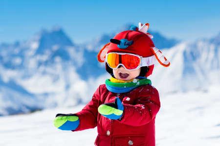 Enfant ski dans les montagnes. Kid à l'école de ski. Sport d'hiver pour les enfants. Vacances de Noël en famille dans les Alpes. Les enfants apprennent le ski alpin. Cours de ski alpin pour garçon ou fille. Amusement en plein air. Banque d'images - 88562665