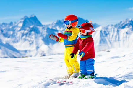 Child skiing in the mountains. Kid in ski school. Winter sport for kids. Family Christmas vacation in the Alps. Children learn downhill skiing. Alpine ski lesson for boy and girl. Outdoor snow fun. Standard-Bild