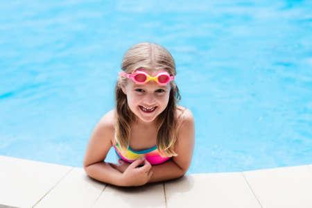 Kind met bril in zwembad. Klein meisje leren zwemmen en duiken in buitenzwembad van tropische resort. Zwemmen met kinderen. Gezonde sportactiviteit voor kinderen. Zon bescherming. Waterplezier.