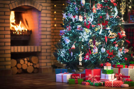 Christmas home interior with tree and fireplace. Traditional living room in country house decorated with lights and candles. Big stone open fire place. Xmas gifts and presents. Reindeer decoration.