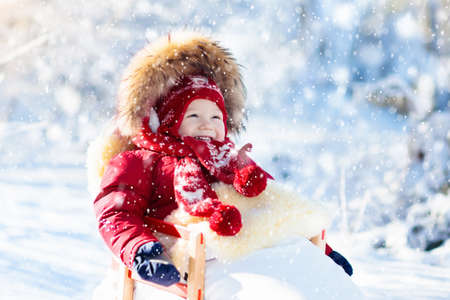 Slee en sneeuwplezier voor kinderen. Baby rodelen in besneeuwde winter park. Kleine jongen in warme rode jas en gebreide muts zitten in schapenvacht voetenzak. Kind op slee. Kind op slee. Familie Kerstvakantie.
