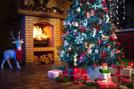 Interior de casa de Navidad con árbol y chimenea. Sala de estar tradicional en casa de campo decorada con luces y velas. Gran chimenea de piedra abierta. Regalos de Navidad y regalos. Decoración de renos Foto de archivo