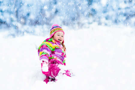 Child playing with snow in winter. Little girl in colorful jacket and knitted hat catching snowflakes in winter park on Christmas. Kids play and jump in snowy forest. Children catch snow flakes