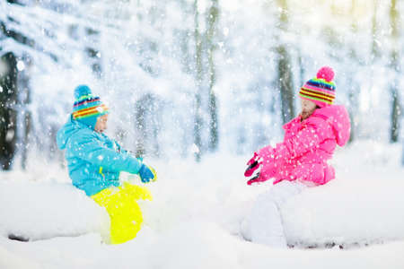 Kids playing in snow. Children play outdoors on snowy winter day. Boy and girl catching snowflakes in snowfall storm. Brother and sister throwing snow balls. Family Christmas vacation activity. Stok Fotoğraf